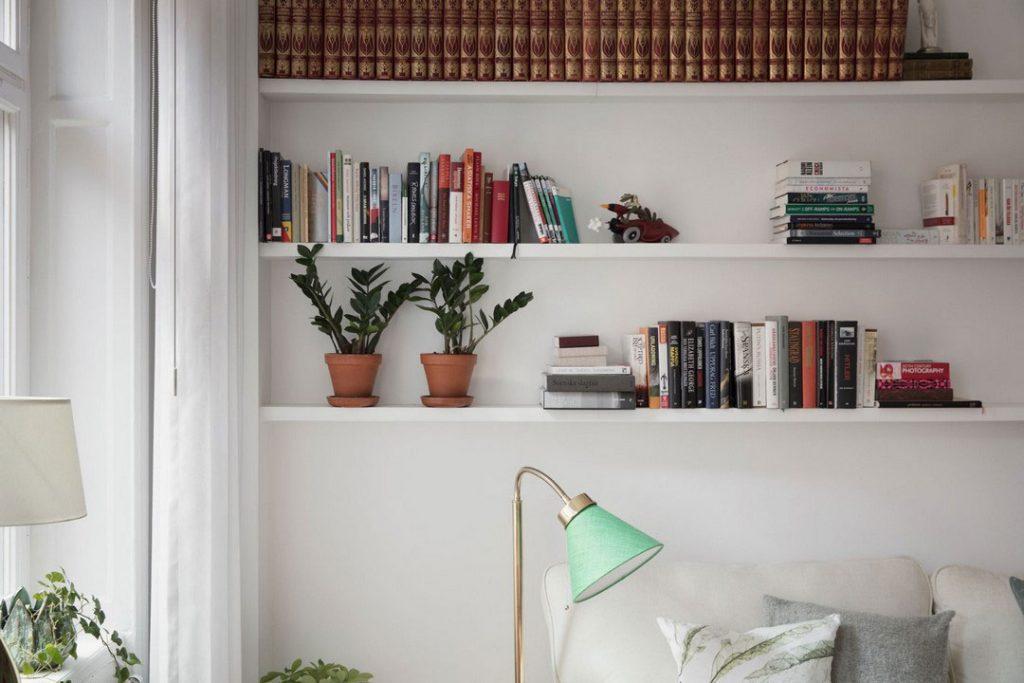 Хранение книг на длинных полках над диваном